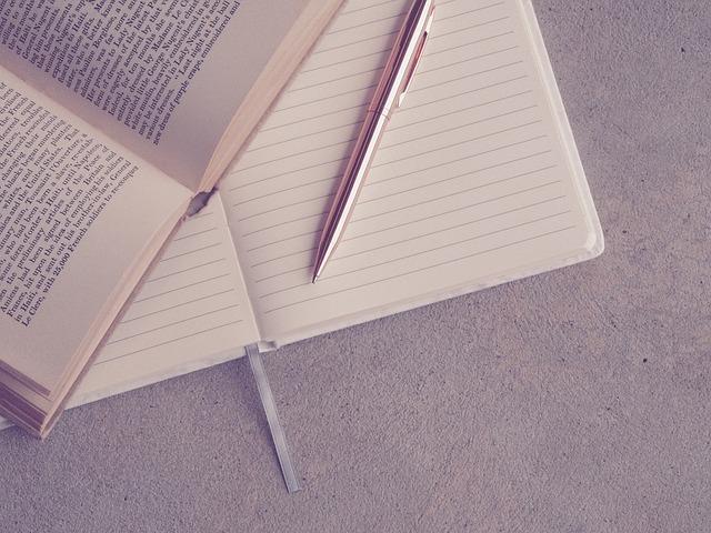 開いている本とノートとペンの写真
