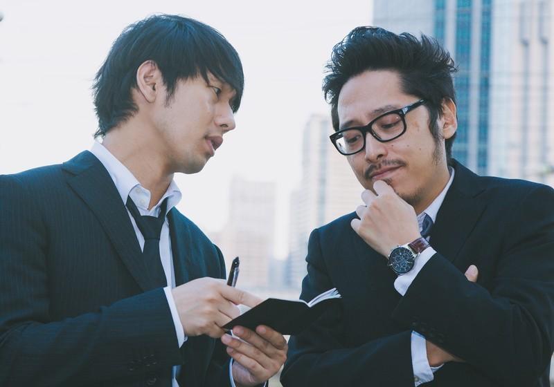スーツ姿の男性2人が会話している