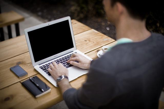 パソコンを使う男性の後ろ姿の写真