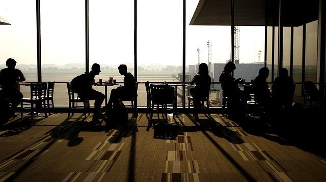 空港ロビーのテーブルにつく人影の写真