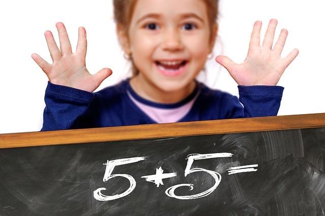 算数をする女の子と黒板。黒板「5 + 5 =」