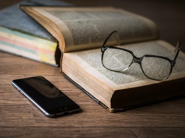 机上にスマートフォンと眼鏡と開かれた洋書がある写真