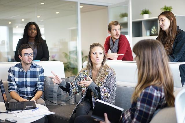 男性2名、女性4名の6名のアメリカ人がオフィスで打ち合わせをしている写真。