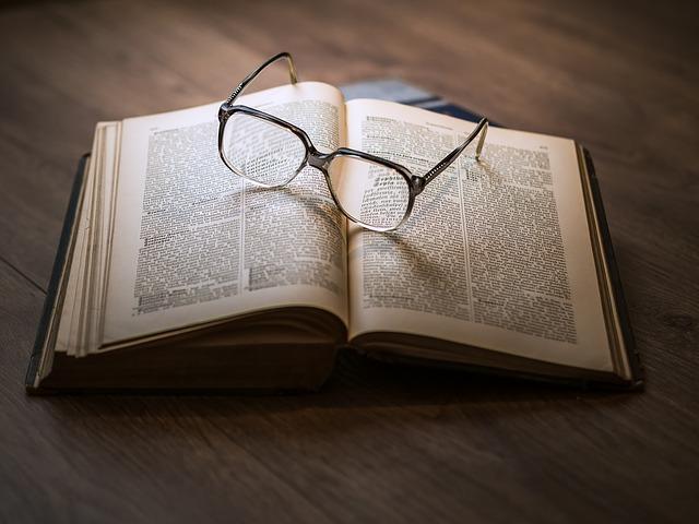 洋書の上に眼鏡が乗っている写真。