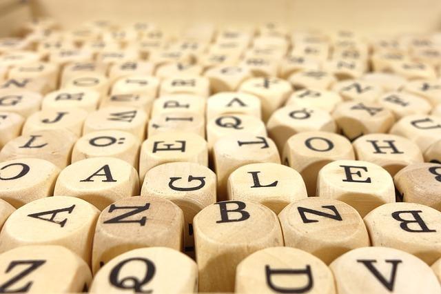 英語のアルファベットが書いてある木目のビーズの写真。