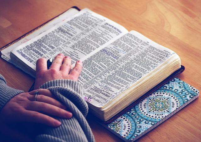 指輪をした女性が机で英語の本を読んでいる写真。