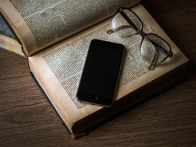 英語の本にスマートフォンとメガネが乗っている写真
