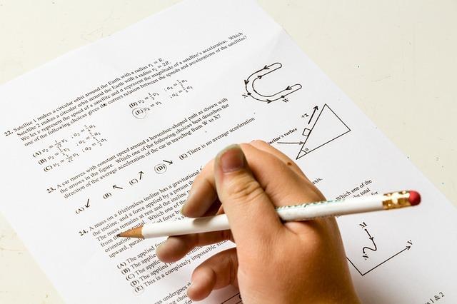鉛筆を持っている手とテスト用紙の写真