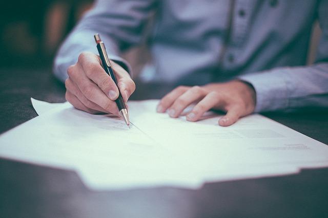 人がペンで紙に書いている画像