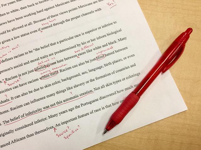 英語の文章が書いてある紙の上に赤いペンが置いてある写真