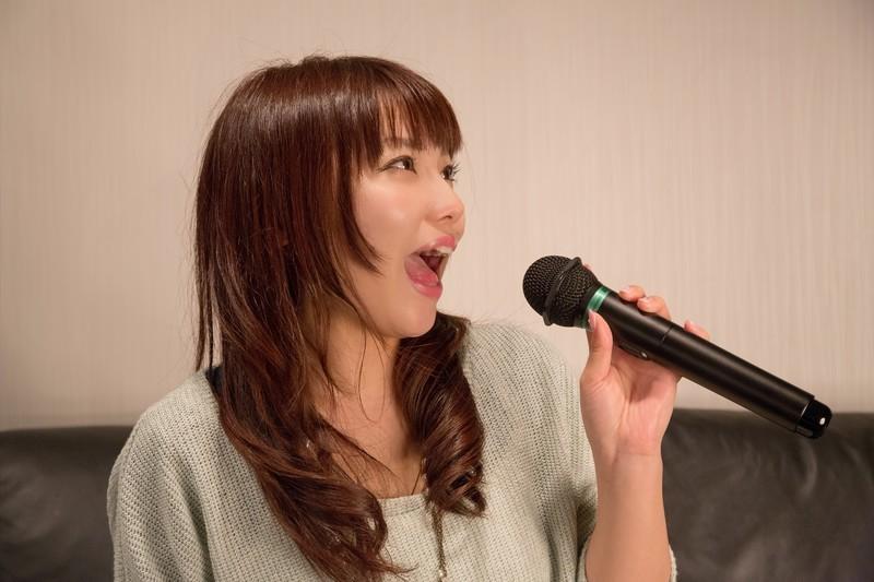 女性がマイクを持って歌っている写真