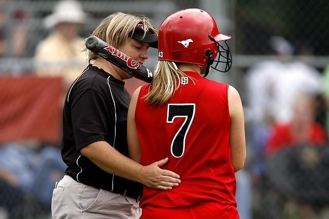 黒いTシャツを着た女性のコーチが、赤いユニフォームを着た背番号7番の女性のバッターを励ましている。