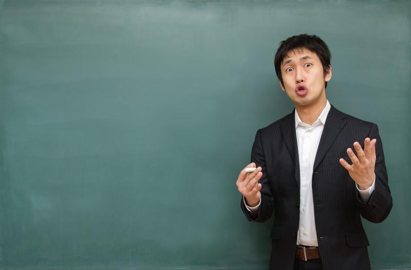 チョークをもって黒板の前で話す男性