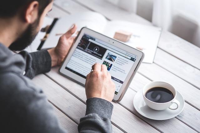 アメリカ人男性がコーヒーを飲みながらタブレット端末を使い英文を読んでいる写真。