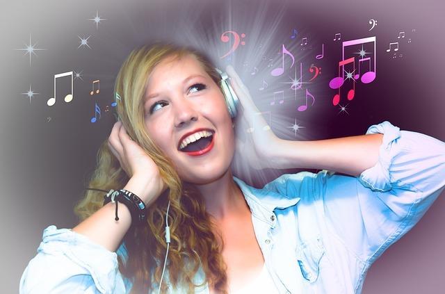 ヘッドホンを付けて音楽を聴きながら歌う女性