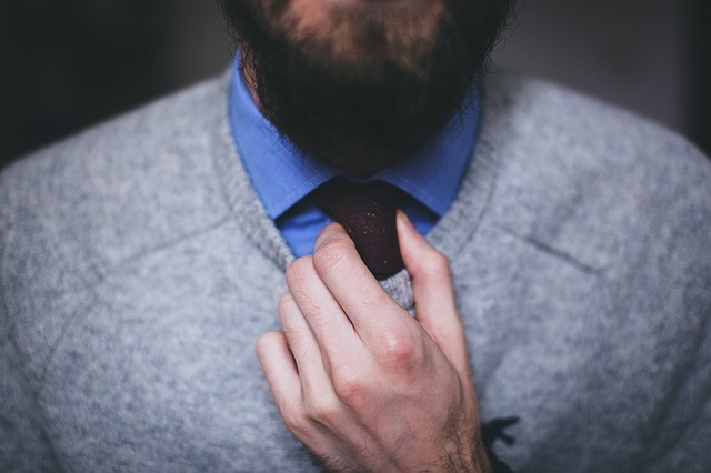 好印象を受けるためにネクタイを正す男。