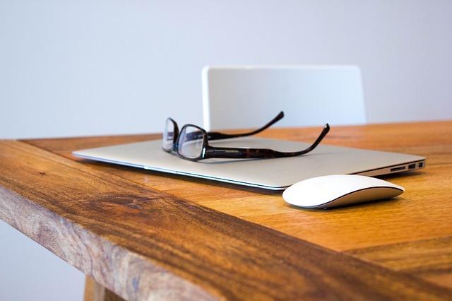 メールを沢山送った後のパソコンの上に置かれたメガネとその横のマウス