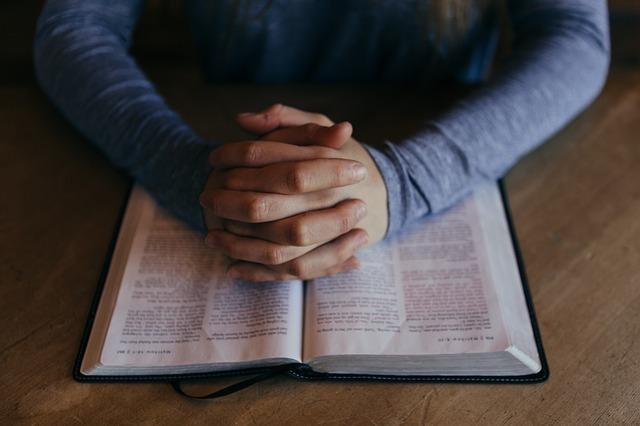 本の上に手を置いて祈っている