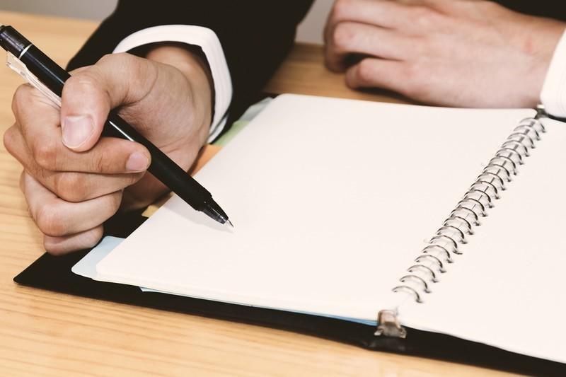 ペンとノートと男性の手
