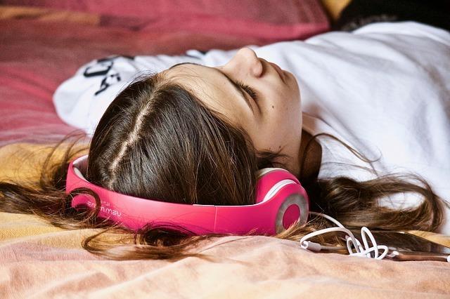 女性がヘッドフォンで何かを聴いている