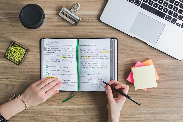 机の上でノートに書き込んでいる手が写っている写真