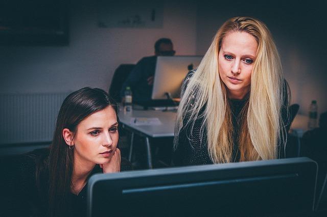欧米人の女性二人がオフィスでPCを見ている