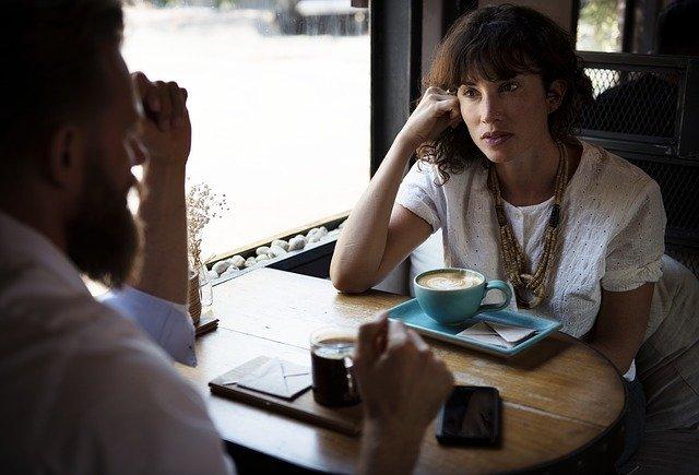 カフェでコーヒーを飲みながら話をしている男女