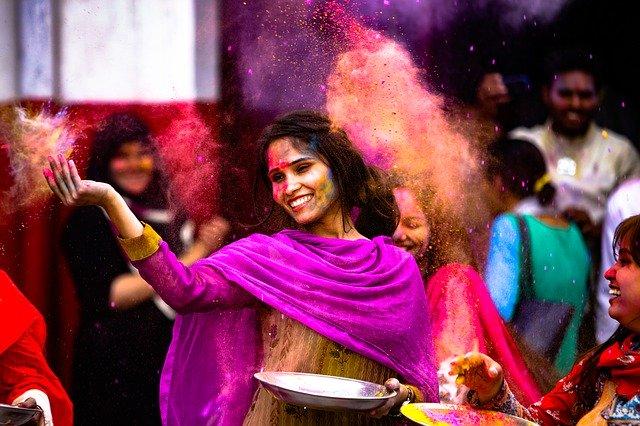 女性が色のついた粉を振りまいている