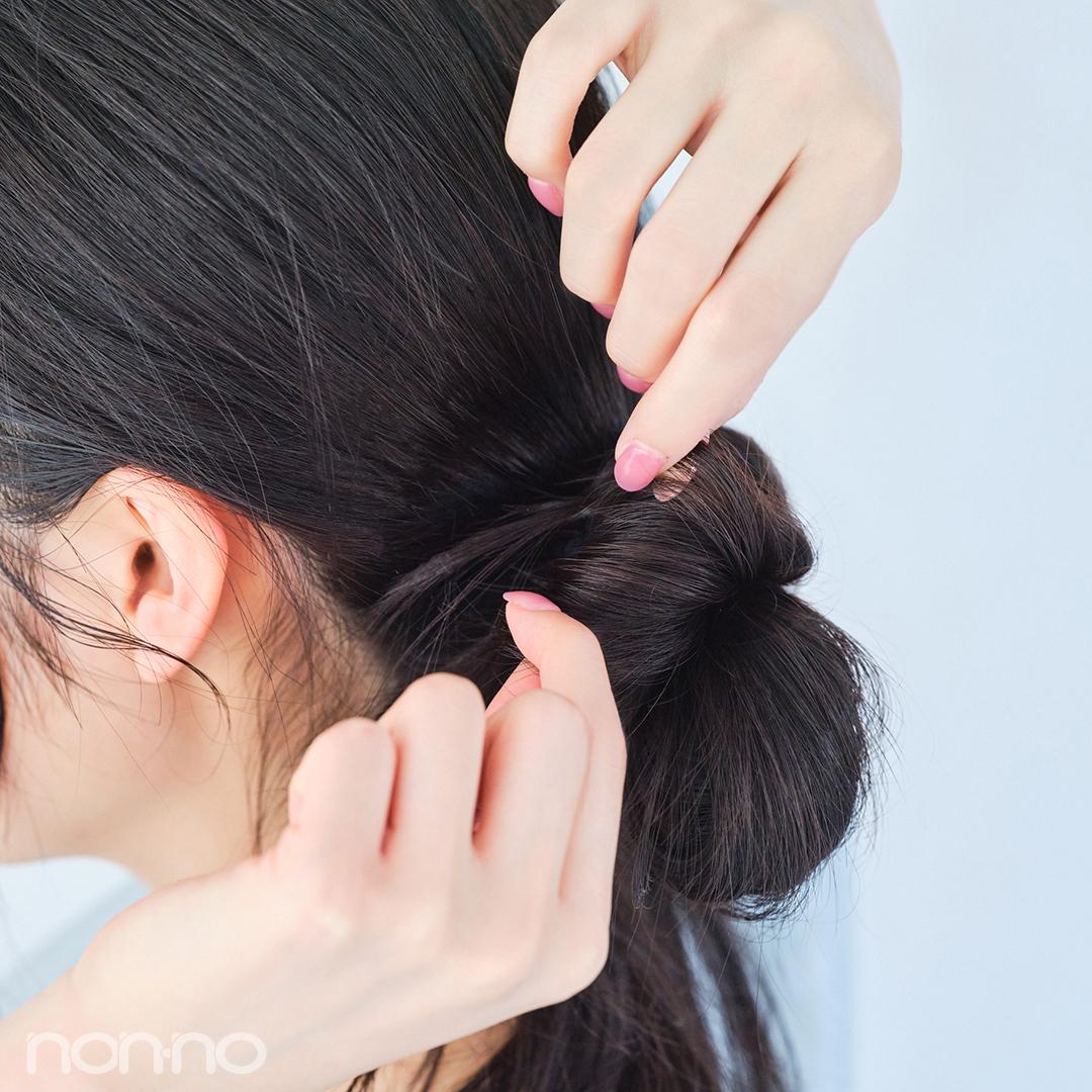 分けておいた毛束を結び目に巻き付けたら、毛先をゴムに絡めて固定する。もうひとつの毛束も同様に。