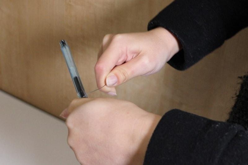 浴室鏡の取り外し方 : ピアノ線をボールペンに巻きつける
