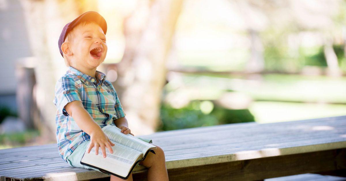 ベンチに座って笑っている子供の画像