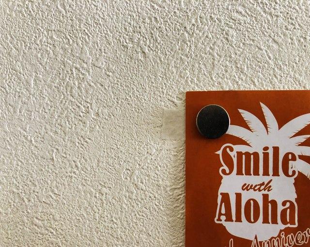 壁にテープと磁石でポスターを貼る画像