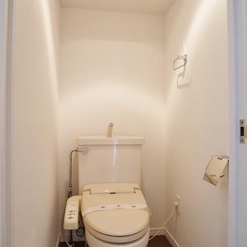 玄関横のトイレ。ウォシュレットと棚板が備え付いています。