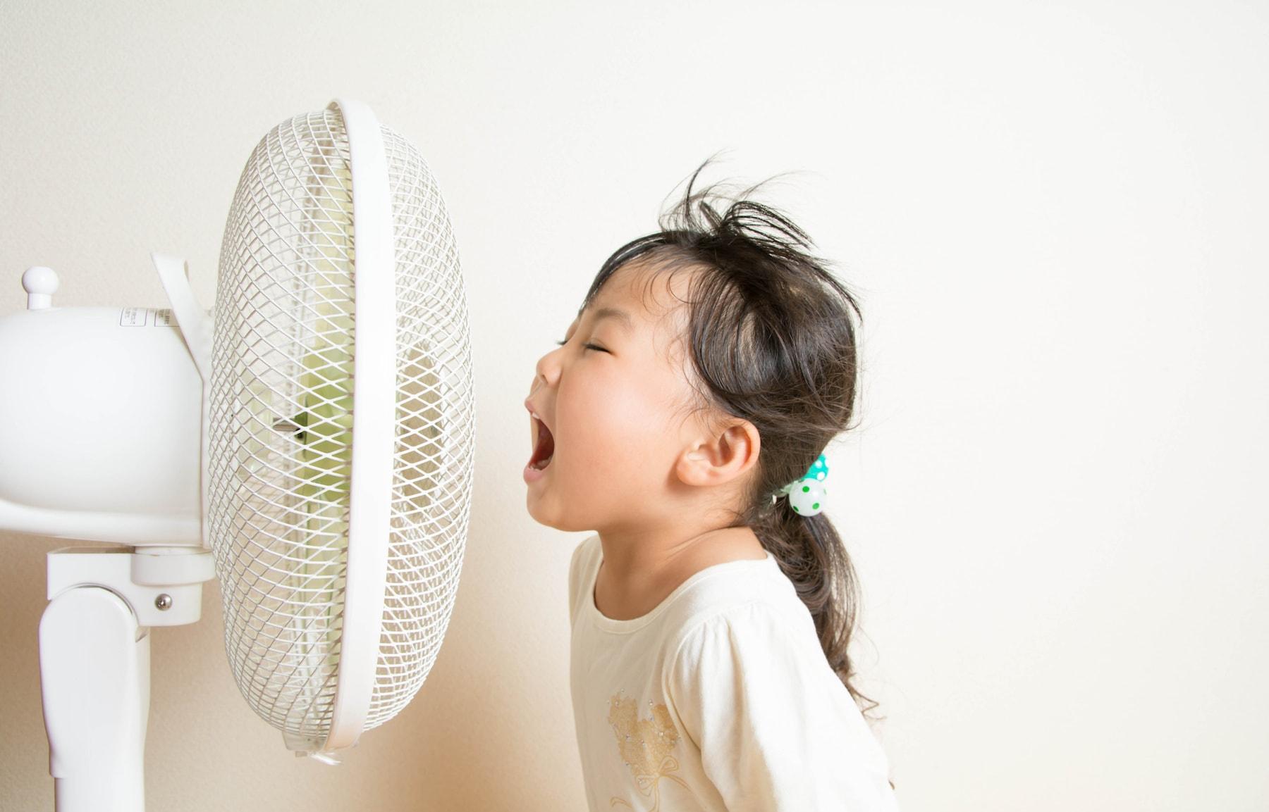 扇風機に当たっている子供