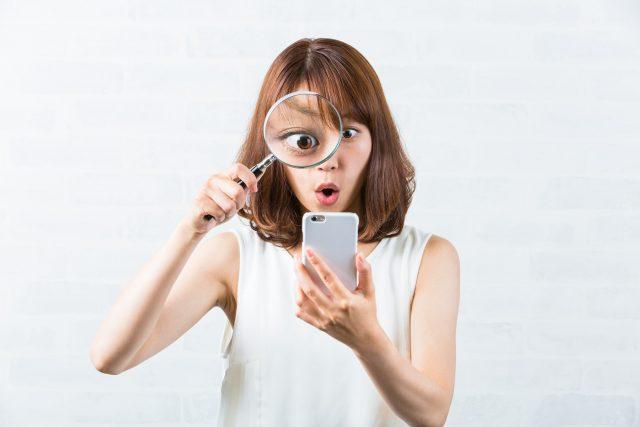 虫眼鏡を使用する女性