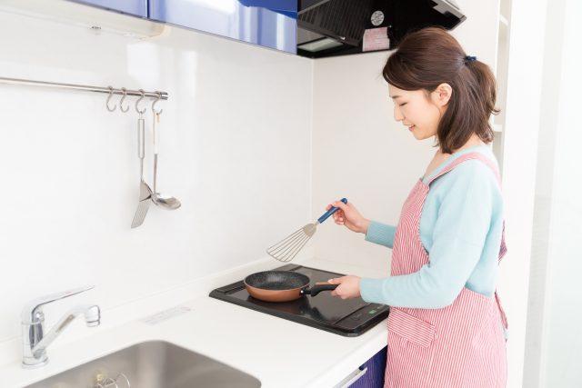IHで料理をする女性