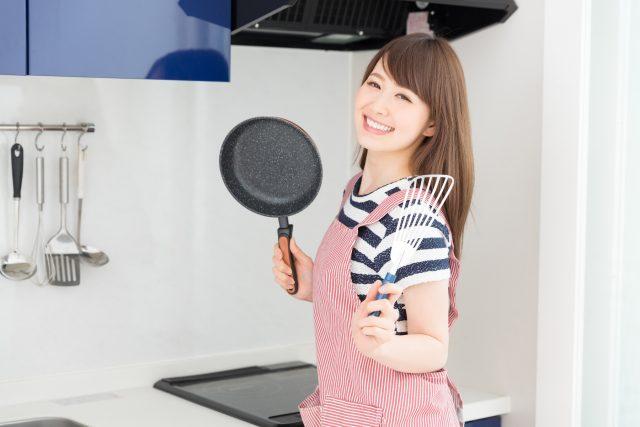 笑顔で料理をする女性