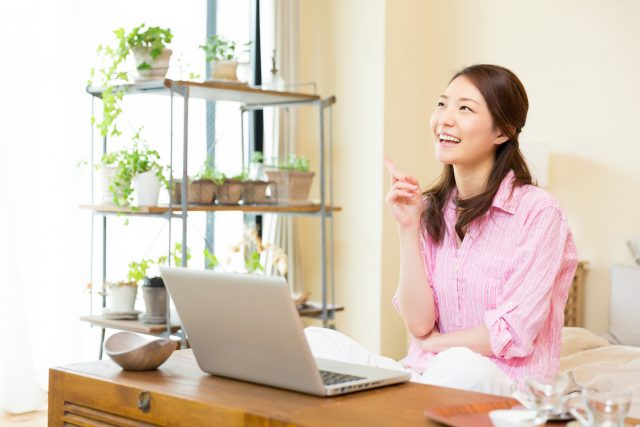部屋でパソコンを見る女性