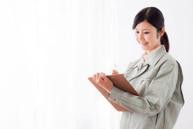 クリップボードを持つ作業員の女性
