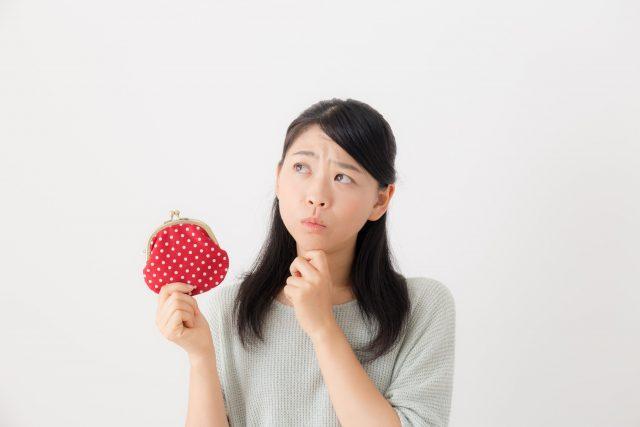 財布を持ち考える女性