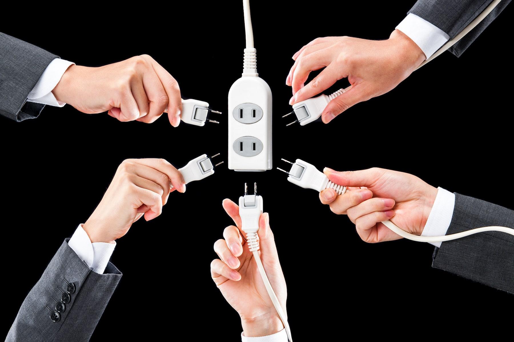 電気のコンセントを持つ人の手