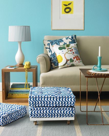 ブルーの壁とスツールのカバーが特徴的なカラフルなリビング