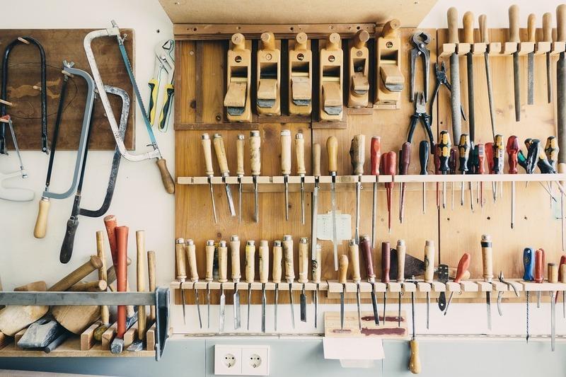 壁面に掛けられた鋸(のこぎり)を始めとする工具の数々