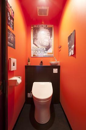 オレンジの壁が特徴的なトイレ