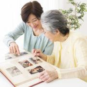 遺品整理時に出てきた写真やアルバムを眺める親子