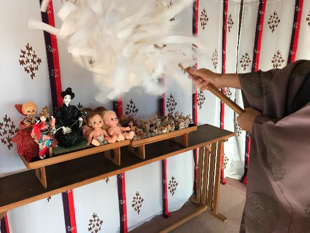 大麻を使って人形供養を行う神主の写真