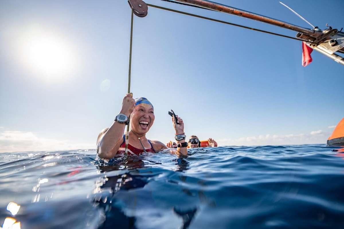 フリーダイビングを終え、海面から顔を出す女性の画像