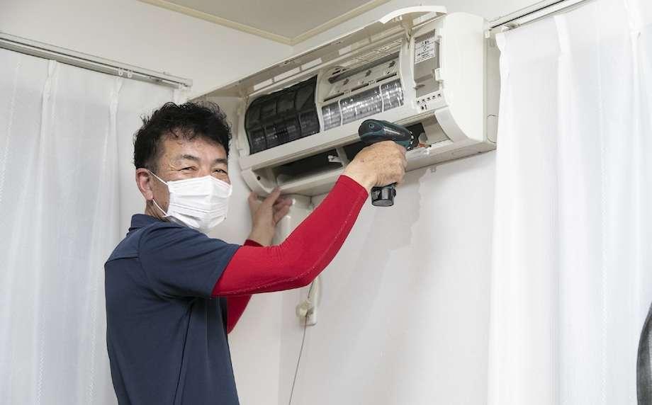 エアコン清掃をしている男性の画像