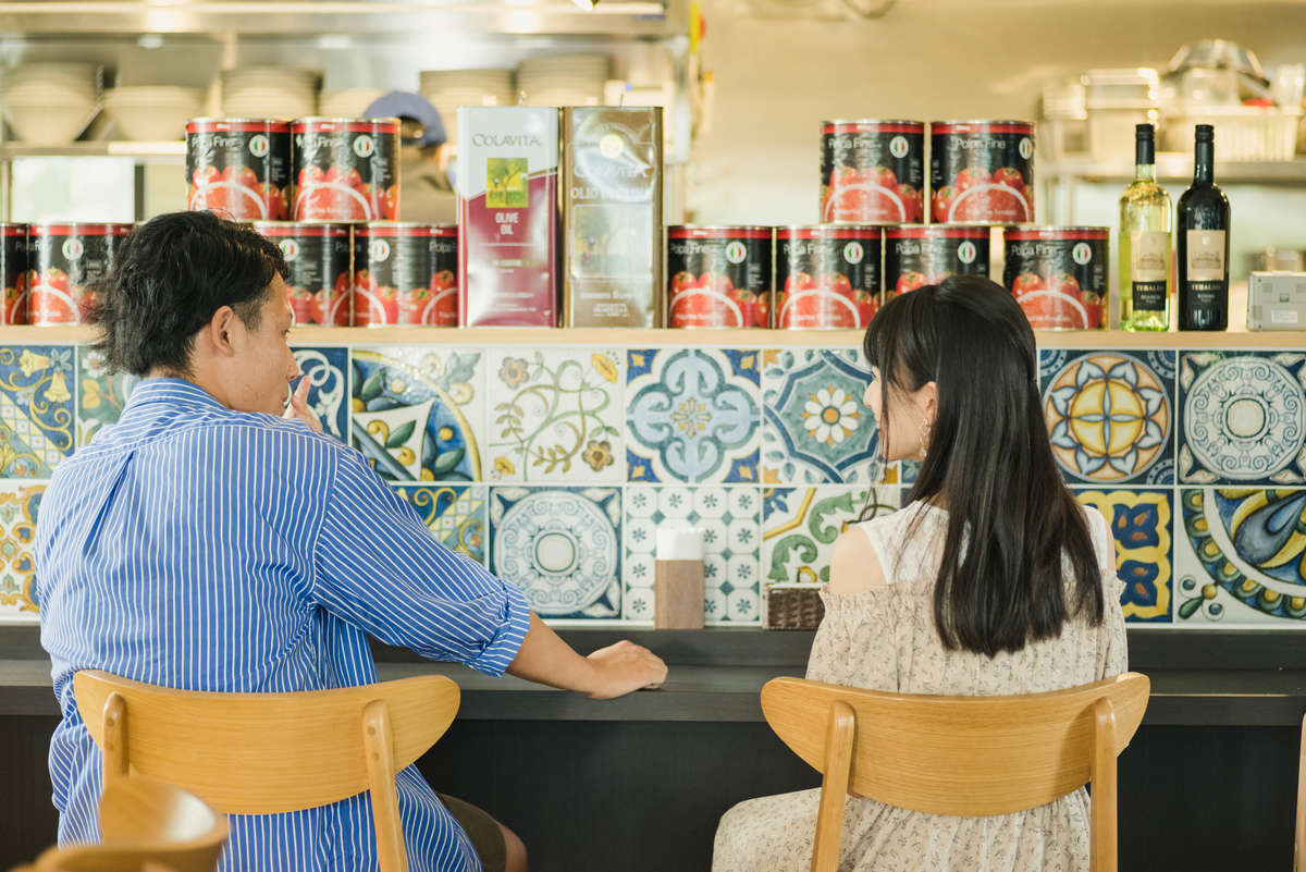 ヌードルキッチンテラコスタのカウンターで歓談する八洲男子(やしまだんし)と読者モデル