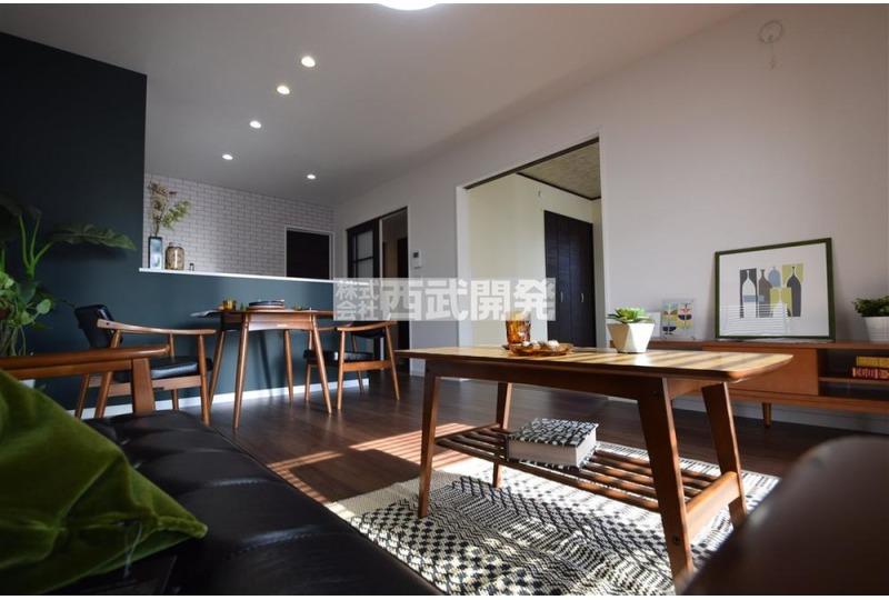 【居間】リビング側から見る対面キッチンにはおちついた色味のクロスを配置。これもまた設置されている家具と調和しております。※掲載写真の家具は販売価格に含まれません。